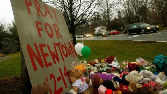 A funeral procession passed tributes left at a makeshift memorial in Newton, Connecticut
