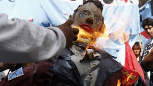A man sets fire to an effigy depicting Britain's Prince William during a demonstration outside the British embassy in Buenos Aires