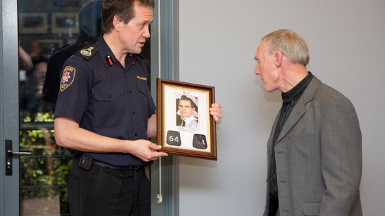 Chief Officer John Bonney presents James Shears's station number lapels to James's father Ed
