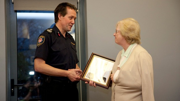 Chief Officer John Bonney presents Alan Bannon's station number lapels to Alan's mother Margaret