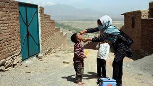 A health worker gives the polio vaccine to a young boy in a remote part of Afghanistan.