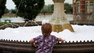 A young boy makes the most of the bubbles.