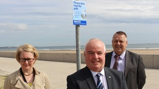 Project Officer Kate Ainger, Councillor Dave Hunter and Enforcement Team Leader Phil Hepburn with one of the posters.