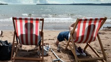 people in deckchairs on Torquay beach