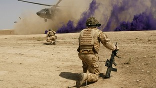 British soldiers cover themselves from dust as a helicopter lands at the Malgeer village in Helmand province
