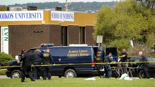 Sheriff's deputies remove a body from outside Oikos University in Oakland