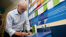 Jeremy Corbyn writes a note to post on the Wonderwall at the Royal Cornwall Hospital.