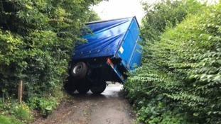 Lorry completely overturns trapping residents in their homes after sat nav leads driver down private road