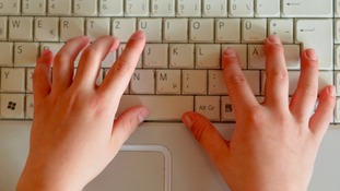 A child types on a keyboard