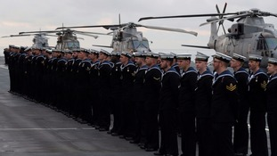 Crew stand aboard HMS Queen Elizabeth as it docks at Portsmouth.