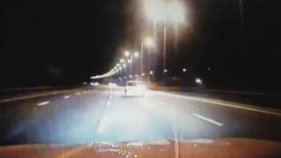 Driver weaves across motorway in front of police car