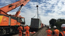 Crane starts work to remove derailed freight train