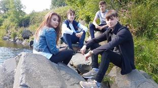Teenagers sitting on rocks
