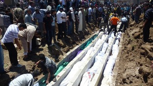 People gather at a mass burial for the victims in the Houla massacre in May 2012