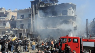 Syrian security members inspecting damaged building after explosions near the intelligence forces in Damascus in March 2012
