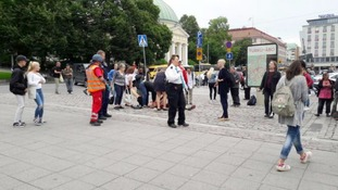 Passers by tend to a victim of a stabbing in the Finnish city of Turku