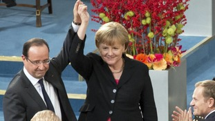 Angela Merkel and Francois Hollande hold up hands during the Nobel Peace Prize ceremony at the City Hall in Oslo December 10, 2012