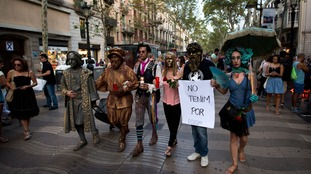 People dressed in costumes, one of them holding a banner reading in Catalan