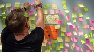 A passerby pastes a slip of paper with a message of peace to a screen near the Las Ramblas.
