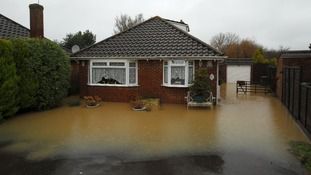 Water covers the front garden of this Hampshire bungalow hiding plant pots in the flood