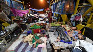 People affected by the flooding sleep at the roadside after being forced to leave their homes.