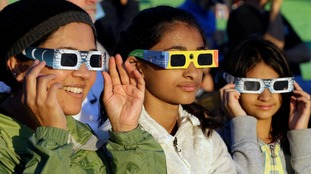 Girls try out glasses to watch the eclipse safely.
