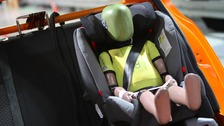 A children-sized crash test dummy is placed in a child car seat at the testing facility of German automobile association.