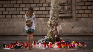 A woman stands at a memorial to the victims of the Las Ramblas attack.