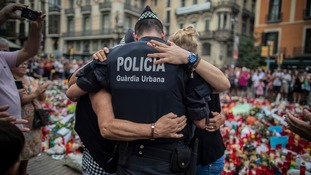 A policeman hugs two people mourning the victims in Las Ramblas.