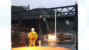 Boat stuck under bridge