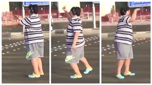 The boy dances in the road.
