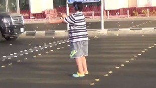 The boy dances in the street.