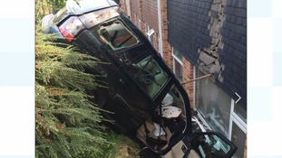 Driver rescued after car gets wedged into a house