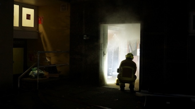 Although smoke was seen coming out of the top of the building, the fire actually in a ground floor rubbish bin room.