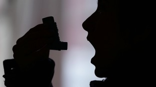 A person using an inhaler