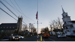 A US flag flies at half mast as a school bus drives past in the town of Newtown on the day of the shootings a week ago