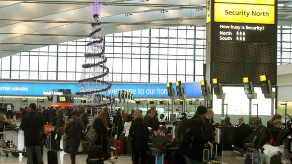 Passengers around the Christmas tree at Terminal 5 of Heathrow Airport as they travel home for Christmas.
