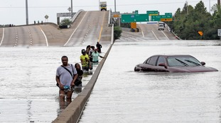 Evacuees wade through a flooded section of Interstate 610 in Houston.