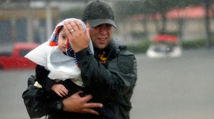 Sgt. Chad Watts holds Madelyn Nguyen, aged two, after rescuing her and her family.