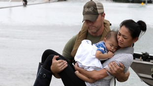 Houston Police SWAT officer Daryl Hudeck carries Catherine Pham and her 13-month-old son Aiden.
