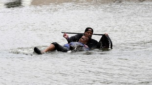A man helps a woman in the Houston floodwaters.