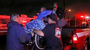 A wheelchair-bound resident is moved from the back of a vehicle in Lake Charles.