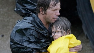 A man carries a girl after being evacuated from their home in Houston.