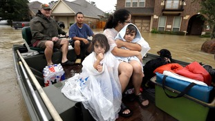 A family is evacuated from their home in Spring, Texas.