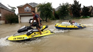 Flood victims are towed to safety by a jet ski in Spring, Texas.