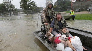 John and Cathy Cservek hold their dogs Lacy and Iggy while being rescued.