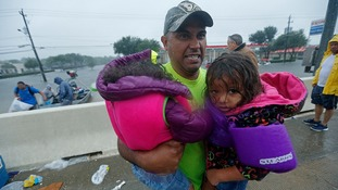 A man carries children after being rescued.