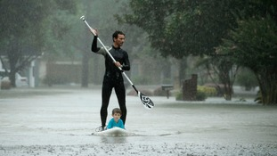 Alexendre Jorge evacuates Ethan Colman, aged four, from a Houston neighbourhood.