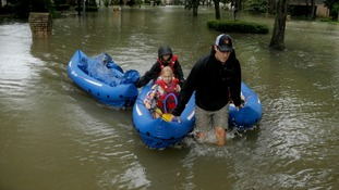 People evacuate a Houston neighbourhood.