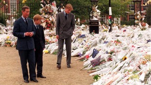 Princes Charles, William and Harry view floral tributes at Kensington Palace in 1997.